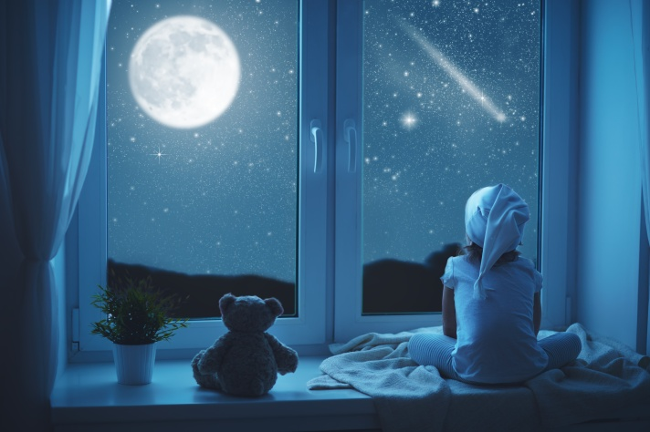 child little girl at window dreaming and admiring starry sky at night